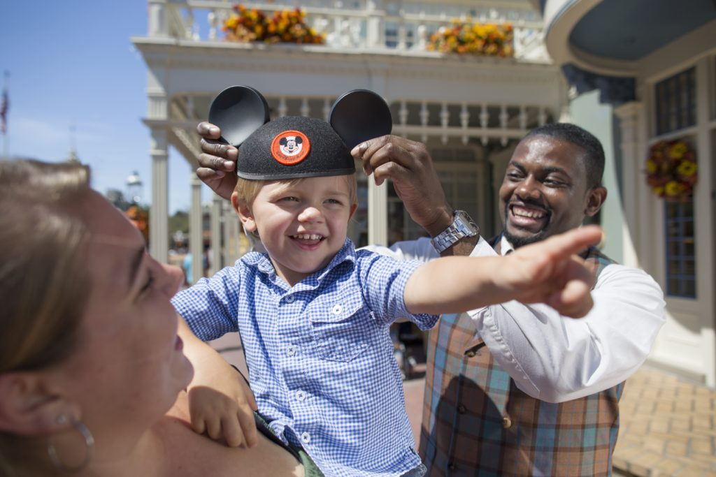 Cast member placing Mickey Ears on a youg boy during his Disney Vacation