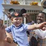 Cast member is crowning a young boy with his first Mickey Ears